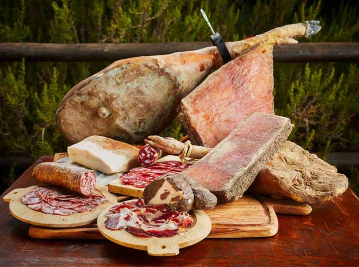 Sliced meats by pork on wooden chopping board